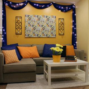 Immagine di un piccolo soggiorno design con pareti arancioni e pavimento in laminato