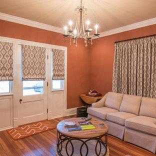 他の地域の中くらいのコンテンポラリースタイルのおしゃれな独立型リビング (オレンジの壁、無垢フローリング、暖炉なし、テレビなし) の写真