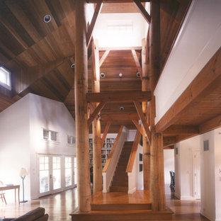 Aménagement d'un salon mansardé ou avec mezzanine montagne de taille moyenne avec un mur blanc, un sol en bois brun, une cheminée d'angle et un manteau de cheminée en pierre.