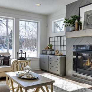 Mittelgroßes, Fernseherloses, Offenes Landhaus Wohnzimmer mit weißer Wandfarbe, Laminat, Kamin, gefliester Kaminumrandung und braunem Boden in Minneapolis