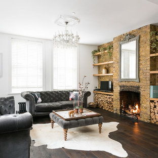 Inspiration for a medium sized farmhouse enclosed living room in London with white walls, dark hardwood flooring, a standard fireplace, a brick fireplace surround, a freestanding tv and brown floors.