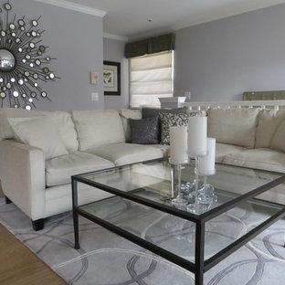 Idéer för att renovera ett litet funkis allrum med öppen planlösning, med grå väggar, en väggmonterad TV och laminatgolv