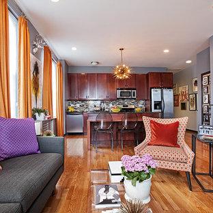 Modelo de salón abierto, bohemio, pequeño, con paredes grises, suelo de madera en tonos medios y pared multimedia