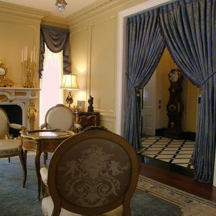 シカゴの大きいヴィクトリアン調のおしゃれな独立型リビング (フォーマル、黄色い壁、濃色無垢フローリング、標準型暖炉、漆喰の暖炉まわり、テレビなし) の写真