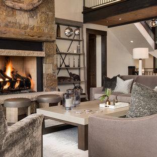Idee per un grande soggiorno classico stile loft con sala formale, pareti beige, pavimento in legno massello medio, camino classico, cornice del camino in pietra e TV a parete