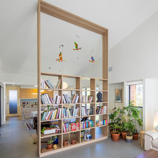 Mid-sized contemporary open concept living room in Canberra - Queanbeyan with a library, grey floor and white walls.