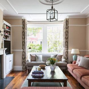 Modelo de salón para visitas cerrado, tradicional, con pared multimedia, paredes marrones, suelo de madera oscura, chimenea tradicional, marco de chimenea de metal y suelo marrón