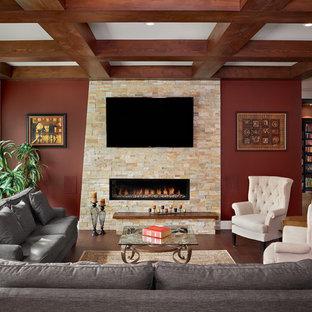 Diseño de salón abierto, tradicional renovado, de tamaño medio, con paredes rojas, suelo de madera oscura, televisor colgado en la pared, chimenea tradicional, marco de chimenea de piedra y suelo marrón