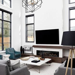 Exemple d'un grand salon chic ouvert avec un mur gris, un sol en bois foncé, une cheminée standard, un manteau de cheminée en pierre, un téléviseur fixé au mur, un sol marron et un plafond décaissé.