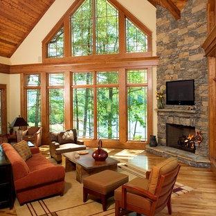 Inspiration pour un salon chalet avec une cheminée d'angle et un téléviseur fixé au mur.