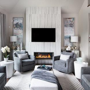 Modelo de salón cerrado, actual, de tamaño medio, con paredes grises, suelo de madera oscura, chimenea lineal, televisor colgado en la pared, marco de chimenea de baldosas y/o azulejos y suelo blanco