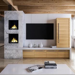 Modelo de salón contemporáneo, de tamaño medio, con paredes blancas, suelo de pizarra, televisor colgado en la pared, marco de chimenea de piedra y suelo beige