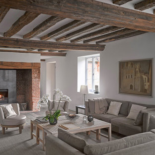 This is an example of a rural living room in London with white walls, a standard fireplace and brown floors.