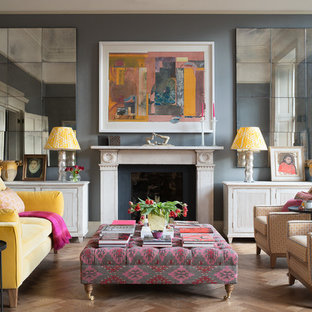 Photo of a bohemian formal living room in London with grey walls, light hardwood flooring, a standard fireplace and beige floors.