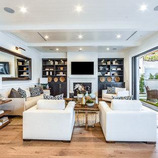 Esempio di un soggiorno classico aperto con pareti bianche, parquet chiaro, camino classico, TV a parete e pavimento beige