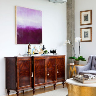 Imagen de salón con barra de bar industrial con paredes blancas y suelo de madera en tonos medios