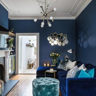 Foto de salón con barra de bar cerrado, clásico renovado, pequeño, con paredes azules, suelo de madera en tonos medios, chimenea tradicional, marco de chimenea de piedra, televisor colgado en la pared y suelo marrón