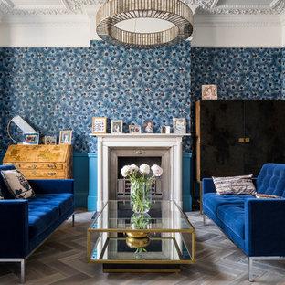 Réalisation d'un salon victorien de taille moyenne et fermé avec un mur bleu, un sol en bois foncé, une cheminée standard, un manteau de cheminée en pierre, aucun téléviseur et un sol marron.