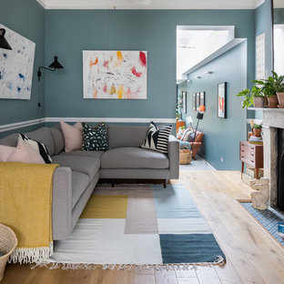 Inspiration for a mid-sized eclectic open concept living room in London with blue walls, light hardwood floors and beige floor.