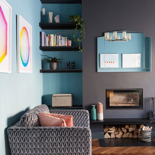 Design ideas for a medium sized contemporary enclosed living room in London with blue walls, medium hardwood flooring and a wood burning stove.