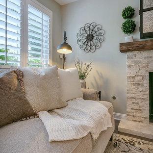 Immagine di un soggiorno stile rurale di medie dimensioni e aperto con pareti grigie, pavimento in legno massello medio, camino classico, cornice del camino in pietra e TV nascosta