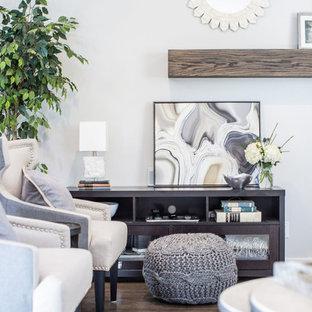 Ejemplo de salón abierto, tradicional renovado, de tamaño medio, con paredes grises, suelo de madera en tonos medios, chimenea de esquina, marco de chimenea de piedra, televisor colgado en la pared y suelo marrón