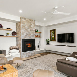 Photo of a contemporary living room in Other with white walls, medium hardwood floors, a standard fireplace, a stone fireplace surround, a wall-mounted tv and brown floor.