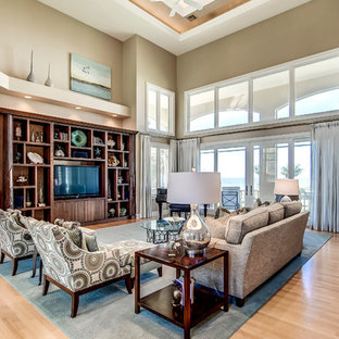 Example of a large coastal open concept medium tone wood floor living room design in Miami with beige walls and a media wall