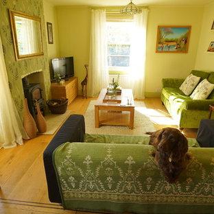 Ejemplo de salón cerrado, de estilo de casa de campo, de tamaño medio, con paredes verdes, suelo de madera en tonos medios, estufa de leña, marco de chimenea de ladrillo y pared multimedia