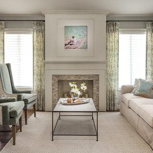 Ejemplo de salón para visitas abierto, clásico, de tamaño medio, sin televisor, con paredes grises, suelo de madera en tonos medios, chimenea tradicional y marco de chimenea de baldosas y/o azulejos