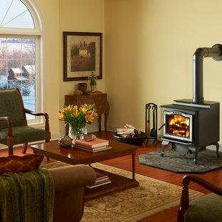 Immagine di un soggiorno stile rurale di medie dimensioni e chiuso con sala formale, pareti beige, parquet scuro, stufa a legna, cornice del camino in metallo, nessuna TV e pavimento marrone