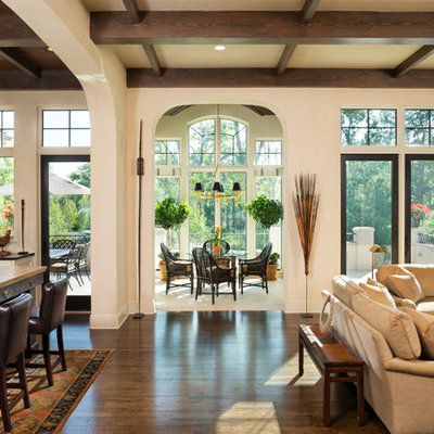 Living room - large traditional open concept dark wood floor living room idea in Minneapolis with beige walls, a standard fireplace, a stone fireplace and a concealed tv