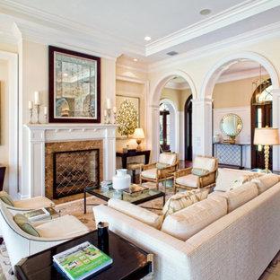 Foto de salón para visitas abierto, clásico, con paredes amarillas, suelo de madera oscura, chimenea tradicional y marco de chimenea de piedra