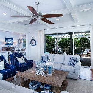 Immagine di un grande soggiorno stile marinaro aperto con pareti bianche, parquet scuro, nessun camino, parete attrezzata e pavimento marrone