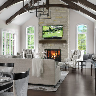 Inspiration for a timeless dark wood floor and brown floor living room remodel in St Louis with white walls, a standard fireplace, a stone fireplace and a wall-mounted tv