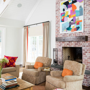 Foto de salón abierto, tradicional renovado, extra grande, con suelo de madera oscura, chimenea tradicional, marco de chimenea de ladrillo, suelo marrón y paredes grises