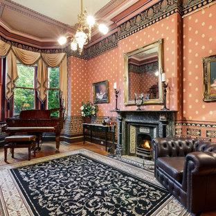 Inspiration for a victorian enclosed living room in Melbourne with a music area, red walls, dark hardwood floors, a standard fireplace, a stone fireplace surround and brown floor.