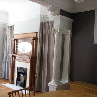 サンフランシスコの小さいヴィクトリアン調のおしゃれなLDK (フォーマル、紫の壁、淡色無垢フローリング、標準型暖炉、木材の暖炉まわり、内蔵型テレビ) の写真