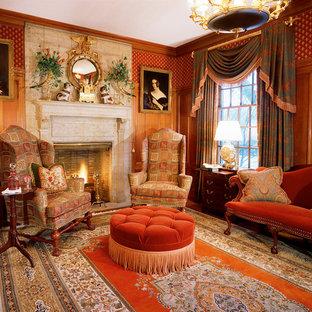 Klassisk inredning av ett mellanstort allrum med öppen planlösning, med ett finrum, röda väggar, en standard öppen spis, en spiselkrans i sten och brunt golv