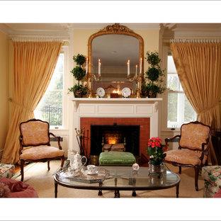 Bild på ett mellanstort vintage separat vardagsrum, med ett finrum, gula väggar, mörkt trägolv, en standard öppen spis, en spiselkrans i tegelsten och brunt golv