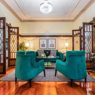 Traditional enclosed living room in Brisbane with white walls, medium hardwood floors, brown floor and panelled walls.