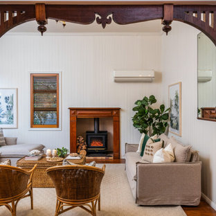 Design ideas for a traditional enclosed living room in Brisbane with white walls, medium hardwood floors, a wood stove, brown floor, timber and planked wall panelling.