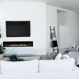 Immagine di un ampio soggiorno minimal stile loft con pareti bianche, pavimento in legno massello medio, camino sospeso, cornice del camino in pietra, TV a parete e pavimento marrone