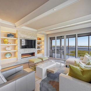 マイアミのコンテンポラリースタイルのおしゃれなLDK (グレーの壁、無垢フローリング、横長型暖炉、積石の暖炉まわり、壁掛け型テレビ、茶色い床、表し梁) の写真