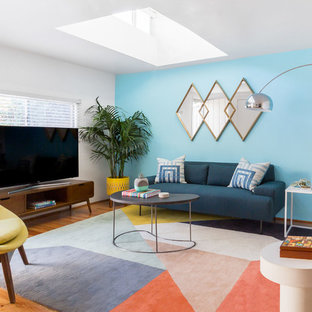 Example of a trendy medium tone wood floor and brown floor living room design in Los Angeles with blue walls and a tv stand