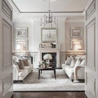 Стильный дизайн: изолированная гостиная комната в классическом стиле с темным паркетным полом, стандартным камином и коричневым полом - последний тренд