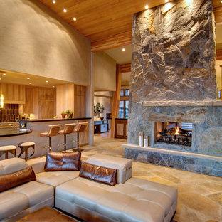 Ejemplo de salón abierto, actual, con chimenea de doble cara y marco de chimenea de piedra