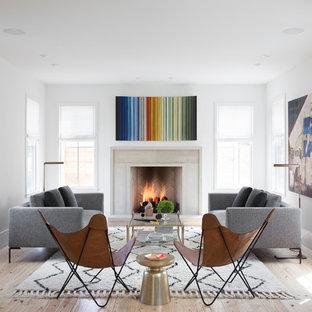 Cette image montre un salon nordique ouvert avec une salle de réception, aucun téléviseur, un mur blanc, un sol en bois clair, une cheminée standard et un manteau de cheminée en pierre.