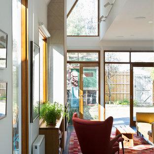 Imagen de salón abierto, actual, con paredes blancas, suelo de linóleo, marco de chimenea de piedra y suelo turquesa
