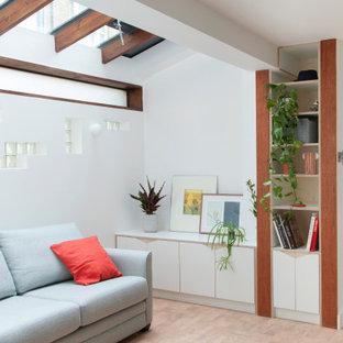 Modelo de biblioteca en casa abierta, contemporánea, pequeña, sin televisor, con paredes blancas, suelo de corcho y suelo marrón